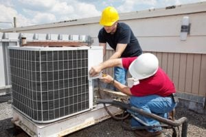 Two men installing a new AC unit